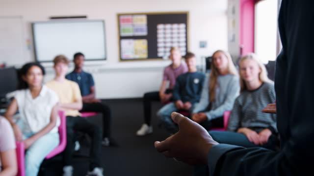 vidéos et rushes de gros plan des mains des enseignants de sexe masculin alors qu'il fait face à la classe d'élèves du secondaire et enseigne la leçon - expliquer