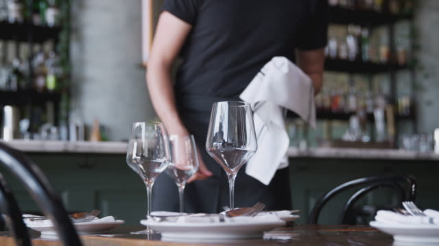 Close Up Of Male Waiter Polishing Cutlery On Table Before Service In Bar Restaurant video