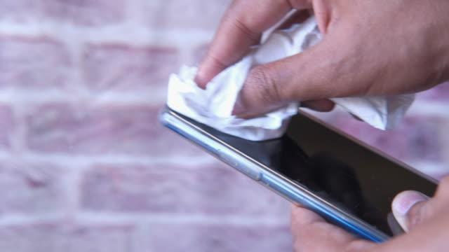 närbild av människan rengöring smart telefon eller förebyggande av sjukdomar - resistance bacteria bildbanksvideor och videomaterial från bakom kulisserna