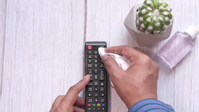 närbild av man rengöring tv fjärrkontroll för förebyggande av sjukdomar - resistance bacteria bildbanksvideor och videomaterial från bakom kulisserna