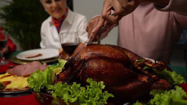 zbliżenie człowieka cięcia indyka na kolację dziękczynną z rodziną - święto dziękczynienia filmów i materiałów b-roll