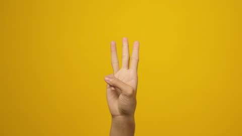 vidéos et rushes de fermez-vous vers le haut de la main d'homme comptant sur ses doigts jusqu'à 3, affichant un, deux, trois signe de main tout en restant au-dessus du fond jaune dans le studio - doigt humain
