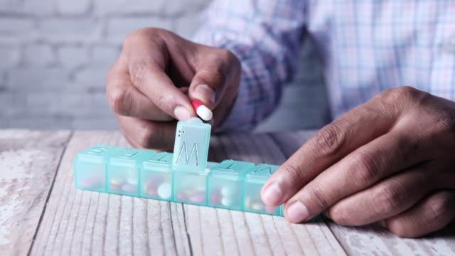 알약 상자에서 약을 복용 하는 남자 손의 클로즈업 - 중년 남자 스톡 비디오 및 b-롤 화면