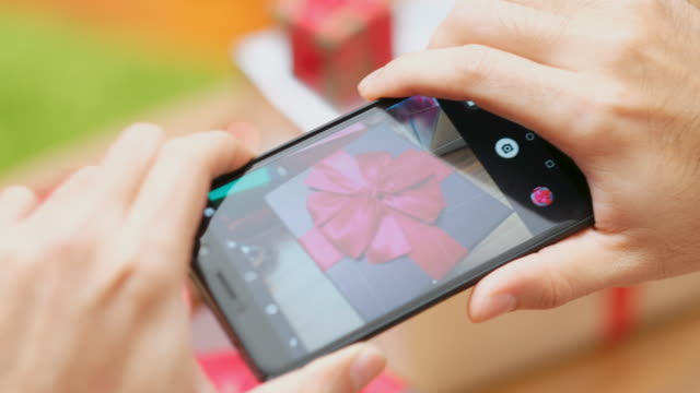 Close up of man hand using phone to take picture Christmas gift box, Blogger photographing Christmas present by smart phone