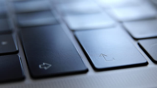 Close up of man hands typing and enter key on a laptop computer keyboard.