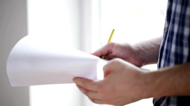 vidéos et rushes de gros plan de l'homme à la recherche et l'écriture dans le presse-papiers - bloc note