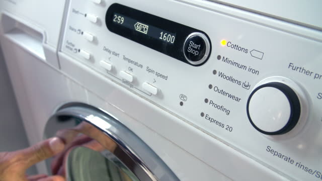 Close Up Of Man Putting Laundry Into Washing Machine Close up of man loading laundry into washing machine and then choosing energy saving setting.Shot on Sony FS700 at frame rate of 100fps dial stock videos & royalty-free footage