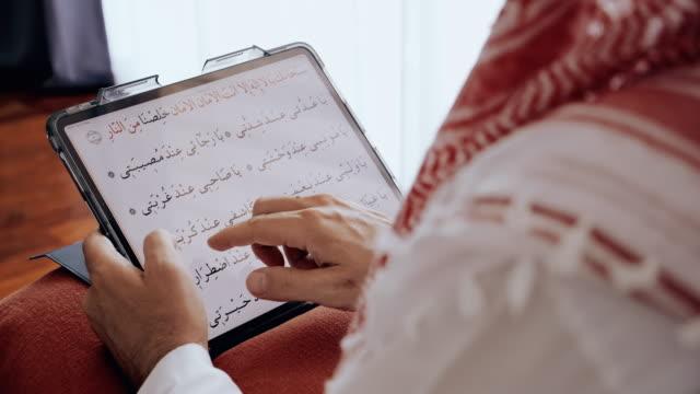 Close up of man reading arab praying text using digital tablet.
