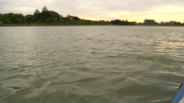 stockvideo's en b-roll-footage met close up van de man zit op een kajak boot en neemt een roeien peddelen naar beneden het meer - paddle