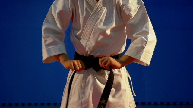 Close up of man tying up knot of black belt on special karate kimono equipment in slow motion video