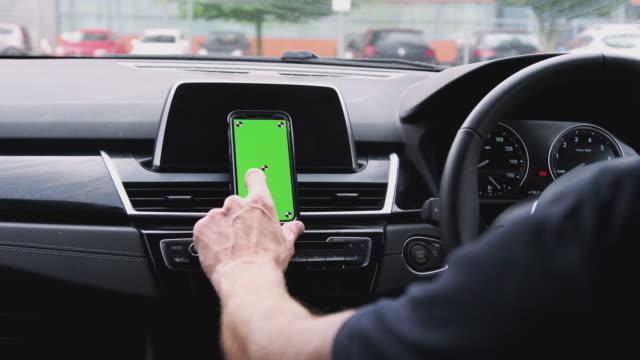 närbild av man med hjälp av mobiltelefon monterad på bilinstrument brädan skjuten i slow motion - stationär bildbanksvideor och videomaterial från bakom kulisserna