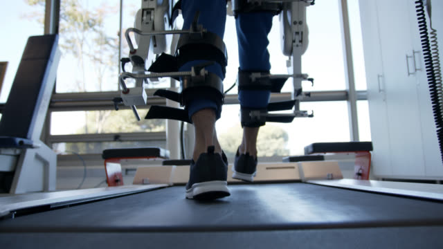 Close up of man walking on treadmill with a help of a exoskeleton robot at a rehab clinic Close up of unrecognizable man walking on treadmill with a help of a exoskeleton robot at a rehab clinic crutch stock videos & royalty-free footage