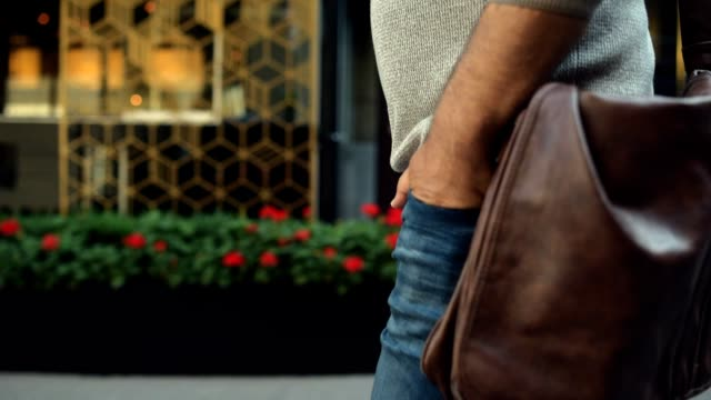 Close up of man walking with hands in pockets video