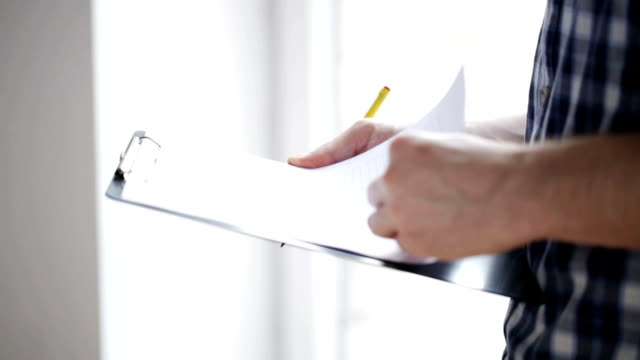 close up of man with measuring ruler and clipboard repair, building, construction and people concept - close up of man with measuring ruler taking notes to clipboard handbook stock videos & royalty-free footage