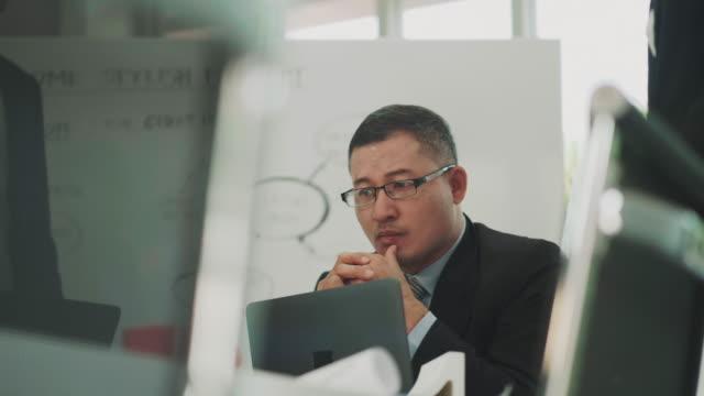 彼のチームは、誤った作業について議論しながら、感情ストレスとマネージャーの顔のクローズ アップ - ミーティング点の映像素材/bロール
