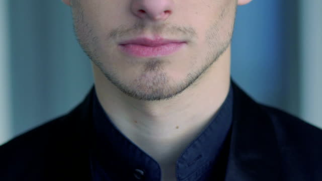 Close up of man's face, neck, lips and shirt. Slow motion video