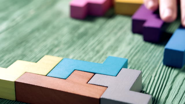 Close up of man's hand folding colorful wooden blocks on the green table background. The concept of logical thinking.