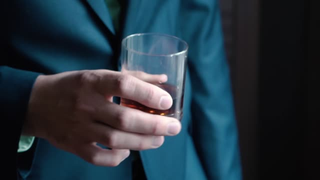 Close up of man's hand holding class of whiskey. Clip video