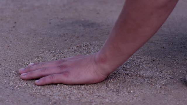 närbild av mannens hand röra sand vid stranden av havet - begreppet hembygd. man håller sin hand över sanden på stranden - begreppet semester och turism. sand på handen vid gröna sandstrand - endast flickor bildbanksvideor och videomaterial från bakom kulisserna