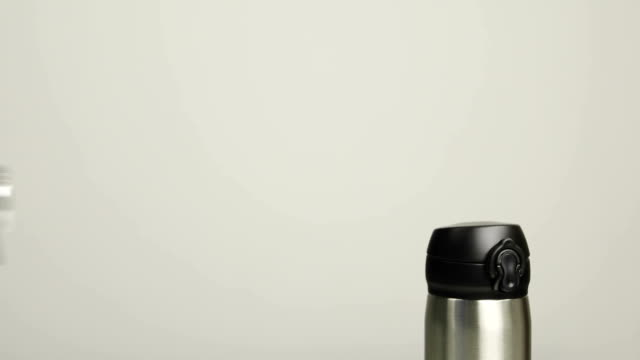 Close up of man's hands putting thermal mug in leather bag on gray background. video