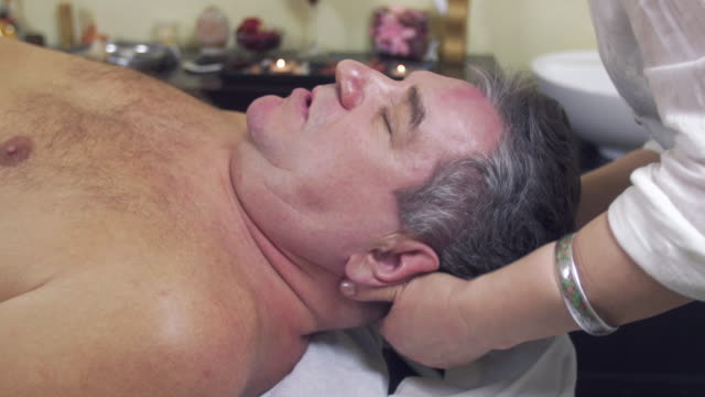 Close up of masseuse hands make healing massage of head to adult fat man Close up of masseuse hands make healing massage of head to adult fat man. Therapeutic. Healthcare pinching stock videos & royalty-free footage