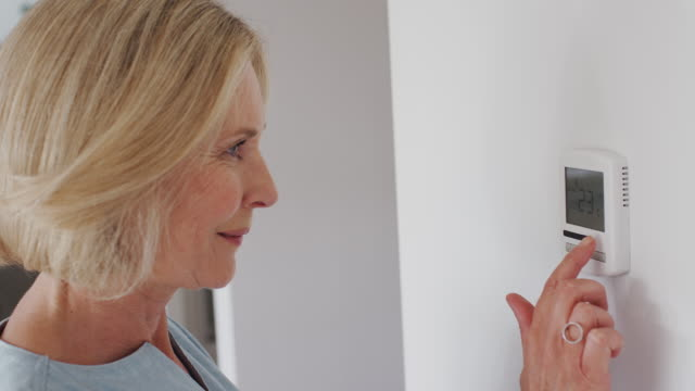 Close Up Of Mature Woman Adjusting Central Heating Temperature At Home On Thermostat video