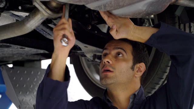 close up of mechanic working under a car using a tool and adjusting something - часть машины стоковые видео и кадры b-roll