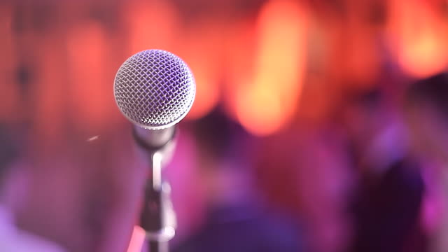 vídeos de stock e filmes b-roll de close up of microphone in concert hall or conference room - orador público
