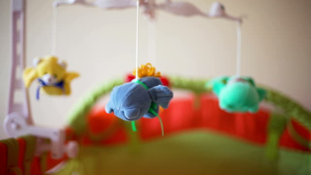 stockvideo's en b-roll-footage met close-up van mobiele roterende over de wieg - baby toy