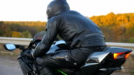istock Close up of motorcyclist racing his motorcycle on autumn country road. Young man in helmet riding on modern sport motorbike at highway. Guy driving bike during trip. Concept of freedom and adventure 1223197376