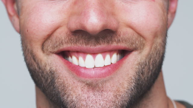 Close Up Of Mouth As Man With Perfect Teeth Smiles At Camera In Studio