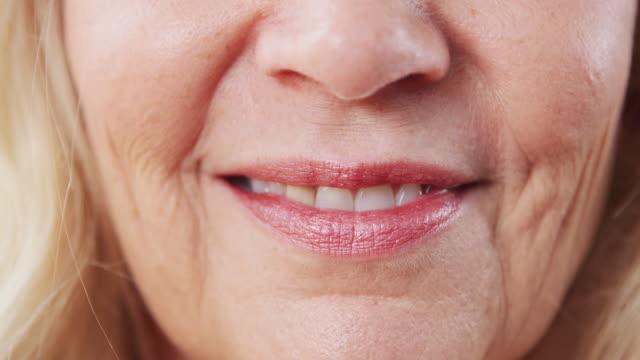 vidéos et rushes de fermez-vous vers le haut de la bouche comme femme mûre sourit à l'appareil-photo dans le studio - bouche
