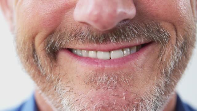 vídeos de stock, filmes e b-roll de feche acima da boca do homem maduro enquanto fala à câmera no estúdio - boca