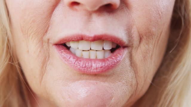 vídeos y material grabado en eventos de stock de close up of mouth of mature woman mientras habla con la cámara en el estudio - boca