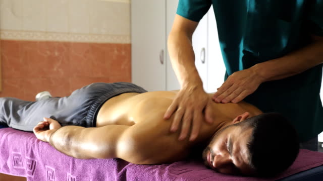 Close up of muscular sportsman lying on massage table and male hands of masseur massaging him shoulders in salon. Professional massagist doing health rubdown of back to athlete in parlor. Slow motion