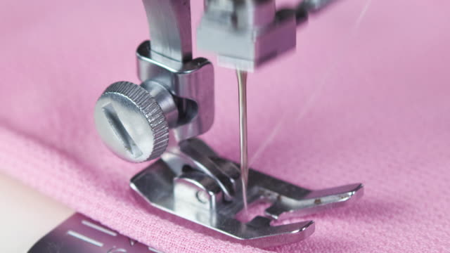 close up of needle moving and sewing on sewing machine. sewing pink material - macchina per cucire video stock e b–roll