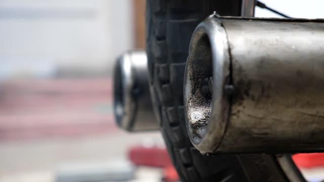 närbild av gamla motorcykel avgasröret avge ångor i luften. slow motion sidovy - wheel black background bildbanksvideor och videomaterial från bakom kulisserna