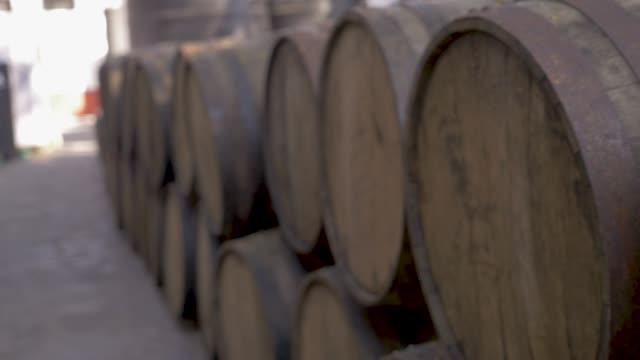 vídeos de stock e filmes b-roll de close up of old oak barrels stacked outside a distillery or winery - barrica