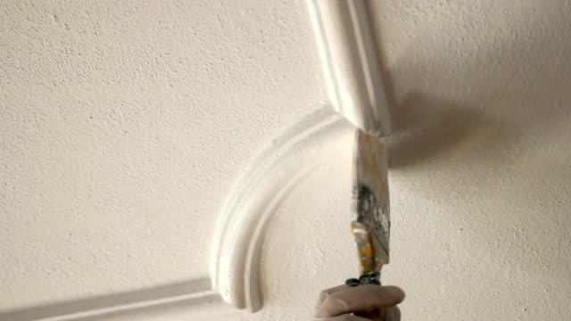 close up of painter hand painting a wall - dekoracja filmów i materiałów b-roll