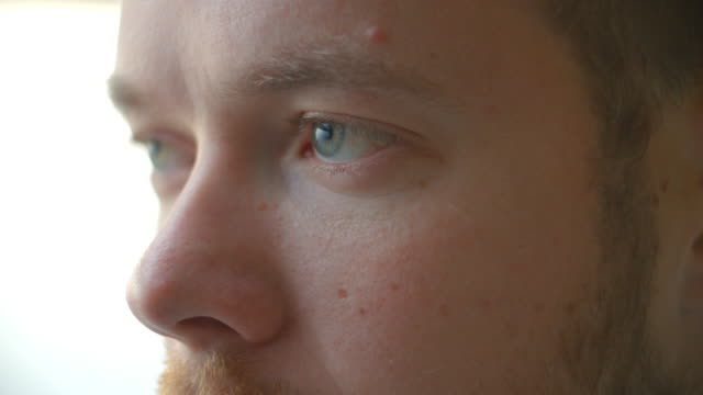 Close up of part of a blue-eyed man's face as he blinks video
