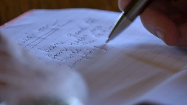 Close up of pen writing letter on table