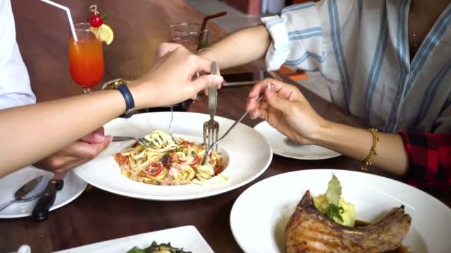 nahaufnahme von menschen nehmen und gemeinsam eine portion spaghetti. freunde, essen schnell greifen - teenage friends sharing food stock-videos und b-roll-filmmaterial