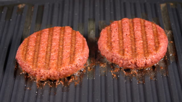 vídeos de stock e filmes b-roll de close up of plant based burger patties on griddle being grilled - meat