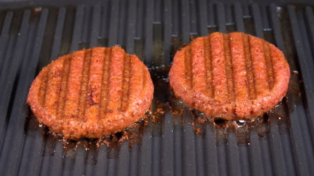 Close up of plant based burger patties on griddle being grilled - video