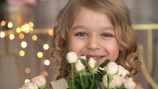 Close up of portrait of little smiling child girl holds bouquet of pink roses, laughs and smells flowers against background of golden blurred garland.