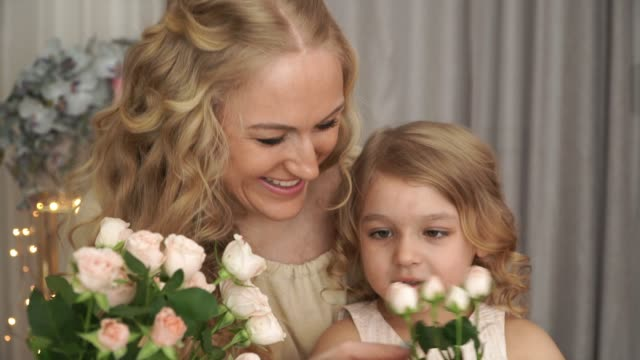 Close up of portrait of smiling mother with daughter sit at table with bouquet of pink roses and learn to count using flower buds