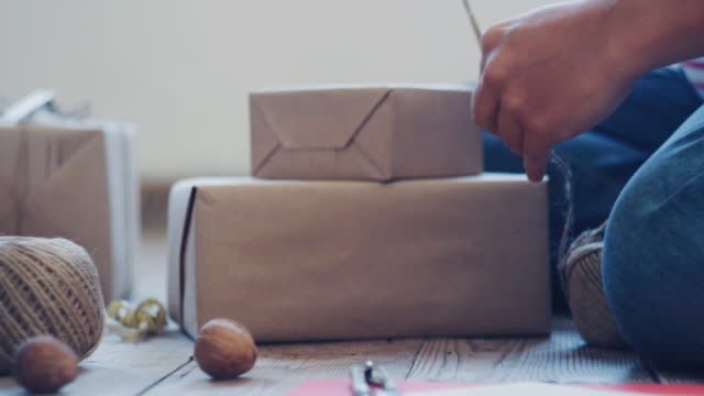 Close up of pregnant woman wrapping Christmas presents at home. Workshop at home during COVID-19 pandemic reality. The new normal.