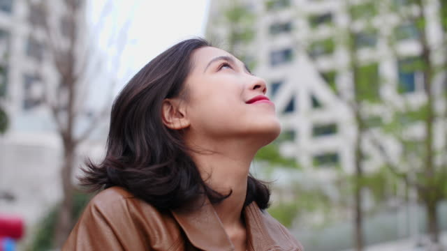 close up of pretty young asian woman looking up smile in slow motion - looking up stock videos & royalty-free footage