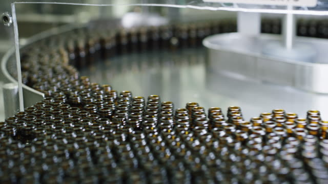 Close up of production of medicines in glassware bottles on automatic lines in a pharmaceutical factory.