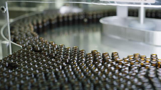 nahaufnahme der herstellung von arzneimitteln in glasflaschen auf automatischen linien in einer pharmazeutischen fabrik. - kosmetik stock-videos und b-roll-filmmaterial